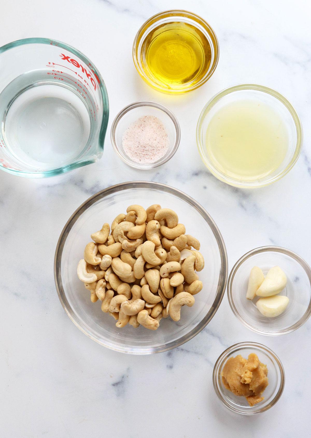 vegan caesar dressing ingredients in glass bowls on marble