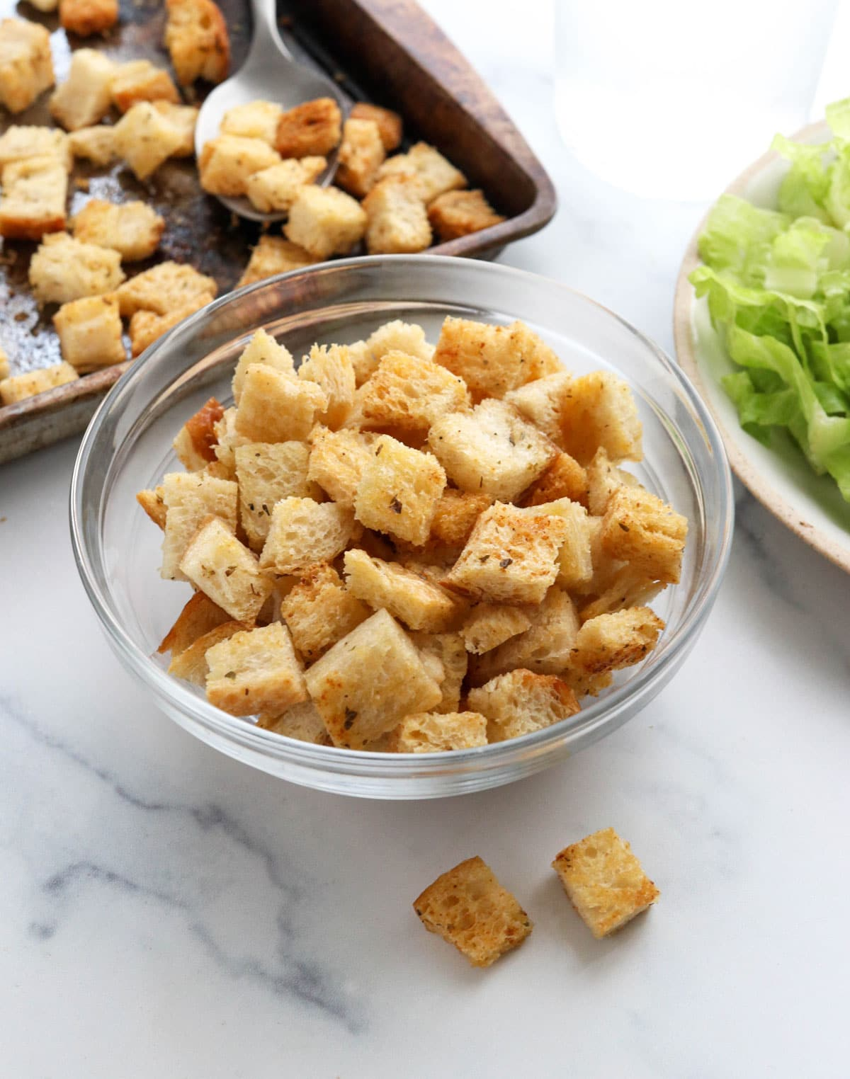 homemade croutons in glass bowl by salad