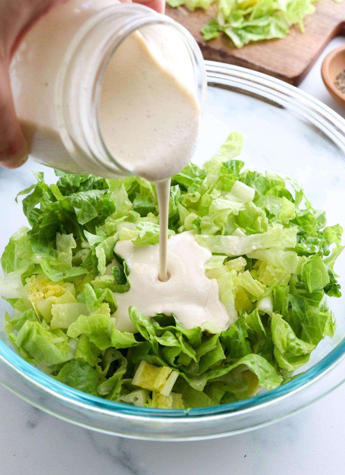 vegan caesar dressing poured on bowl of lettuce