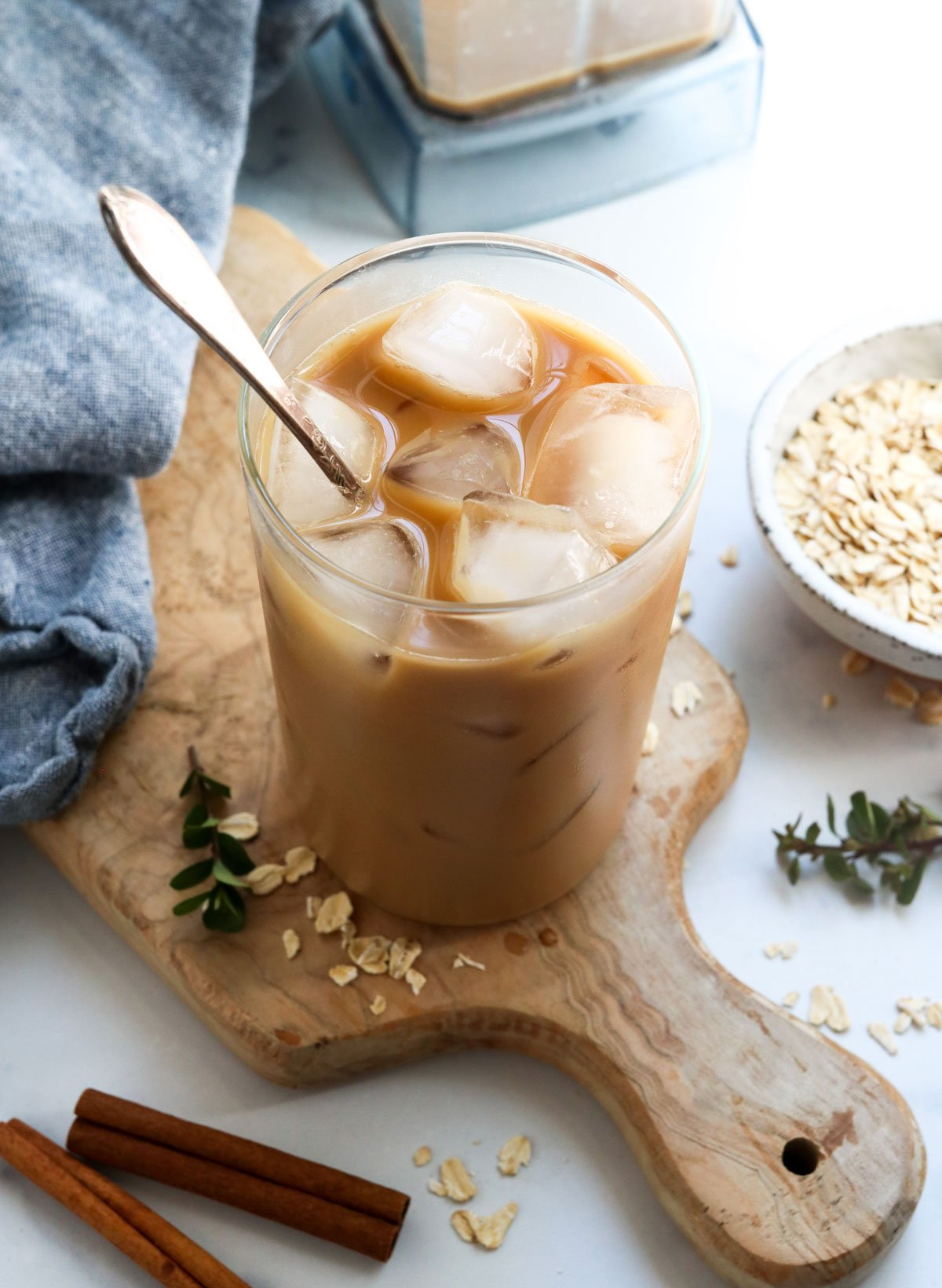 iced oat milk latte with spoon in glass