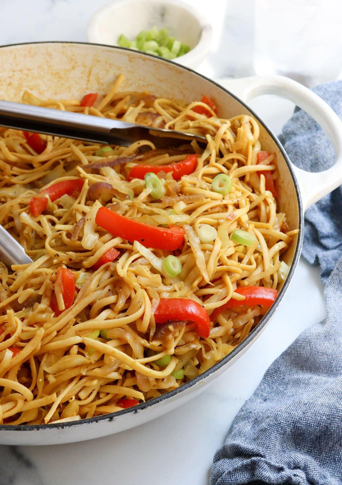 singapore noodles in pan with tongs